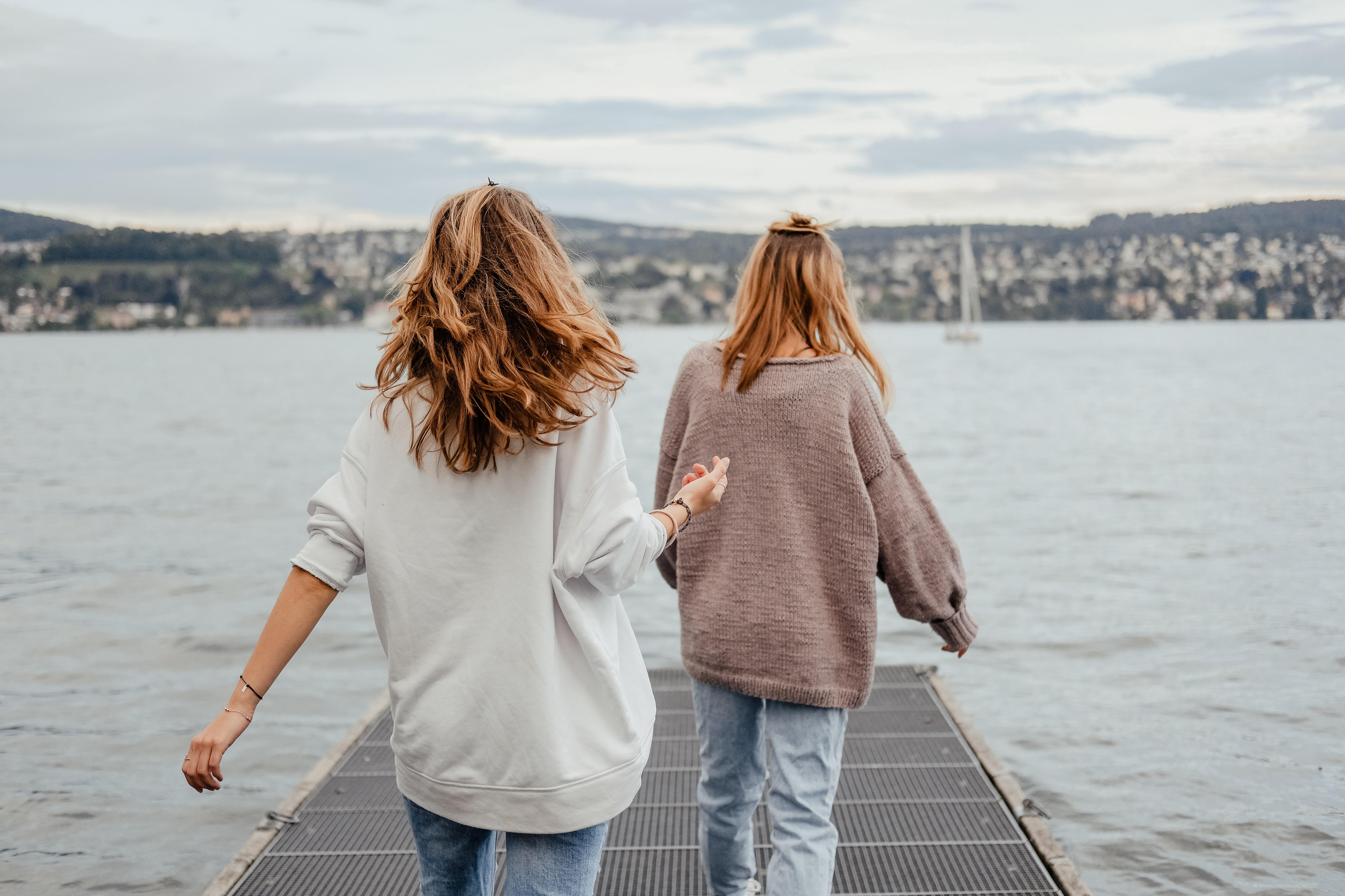 Two women having fun on a bridge.