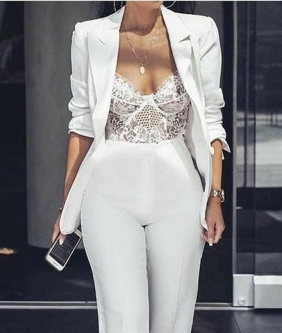 Woman wearing blazer and white lacy top.