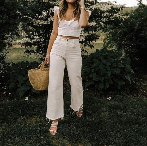 Woman holding beach bag wearing white.