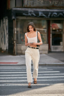 Woman wearing casual clothing while walking down the street.