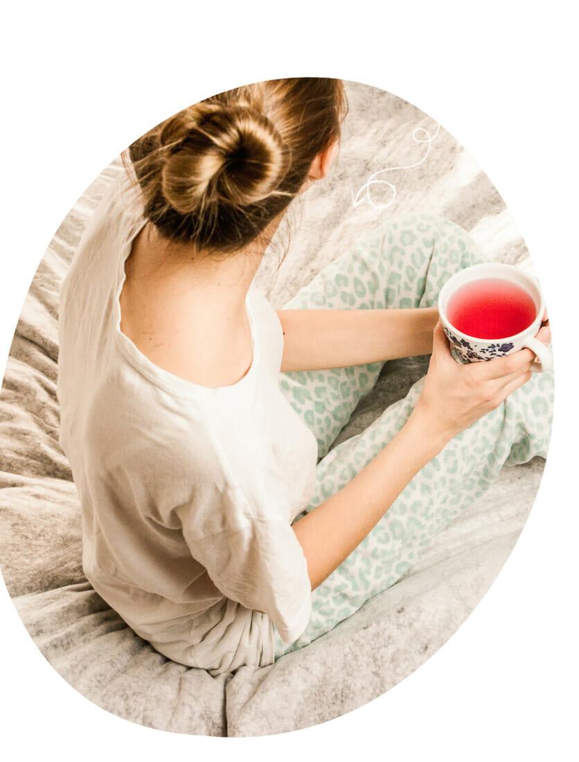 Woman drinks tea in bed wearing comfortable pajamas.